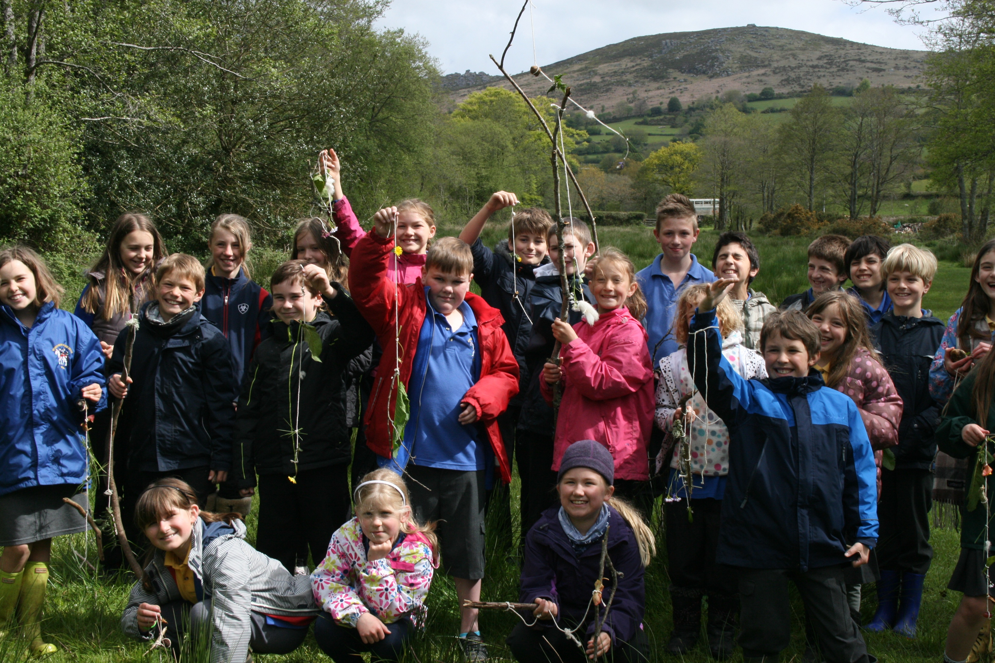Children hold up their creations of items they have found on a walk